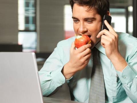 Человек есть яблоко, говорит по телефону и смотрит на монитор